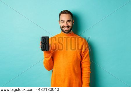 Handsome Bearded Guy In Orange Sweater, Showing Smartphone Screen And Smiling, Showing Promo Online,