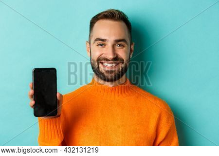 Close-up Of Handsome Bearded Guy In Orange Sweater, Showing Smartphone Screen And Smiling, Showing P