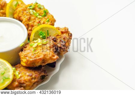 Delicious Onion Bhaji Fritters Served On Ceramic Plate With White Dip