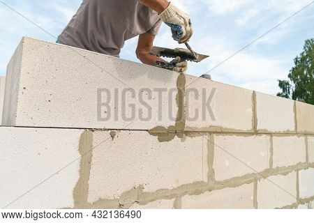 Worker Wipes The Seams With A Spatula Outside The House Of Blocks. Bricklayer Worker Laying White Bl