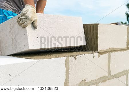 Builder Makes A Concrete Wall With Cement Blocks On The Construction Site Of A House. Concept Of Bui