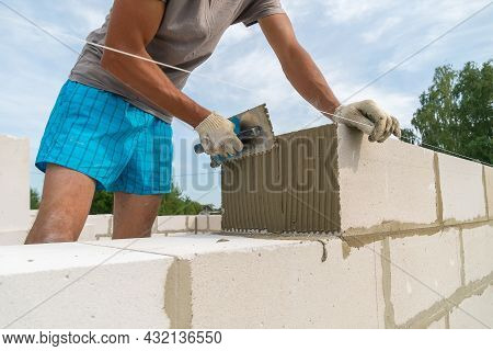 Builder Uses A Notched Trowel To Apply The Cement Mixture To The Side Of The Building Block. Concept
