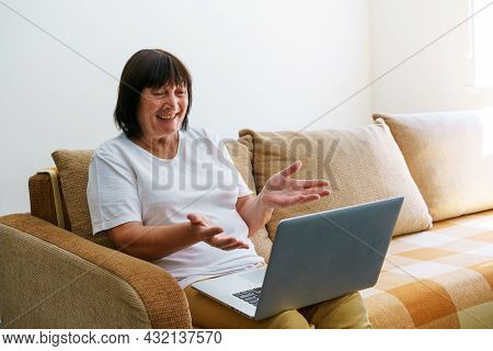 Elderly Mature Woman Using Wireless Laptop Apps Browsing Internet Sitting On Sofa Smiling Middle Age
