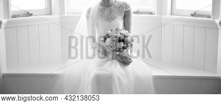 A Bride Holding Her Bouquet In Dreamy Soft Window Light As She Poses Before Her Wedding - Monotone I