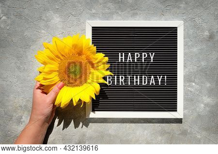 Text Happy Birthday On Text Board. Autumn Natural Decorations. Yellow Sunflower In Hand. Flat Lay, T