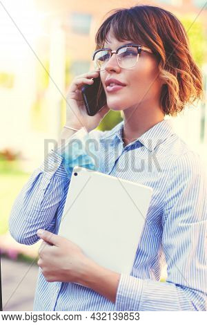 Young Caucasian Businesswoman Takes Down Mask On Arm And Calling In Park During Pandemic