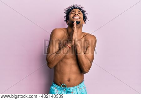 Young african american man with beard wearing swimsuit begging and praying with hands together with hope expression on face very emotional and worried. begging.