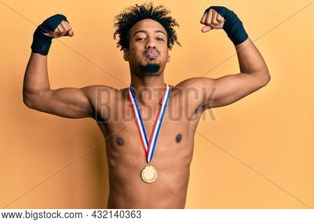 Young african american man with beard wearing first place medal on boxing competition puffing cheeks with funny face. mouth inflated with air, catching air.
