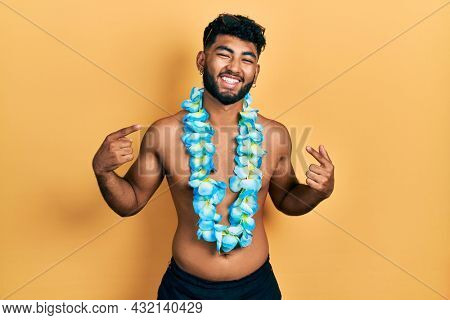 Arab man with beard wearing swimsuit and hawaiian lei looking confident with smile on face, pointing oneself with fingers proud and happy.