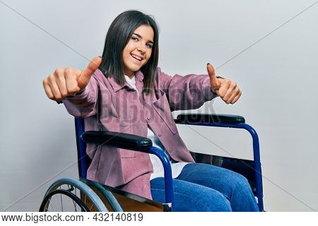 Young brunette woman sitting on wheelchair approving doing positive gesture with hand, thumbs up smiling and happy for success. winner gesture.