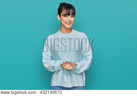 Young hispanic woman wearing casual clothes with hands together and crossed fingers smiling relaxed and cheerful. success and optimistic