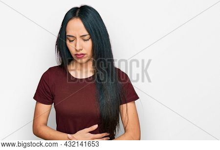 Young hispanic girl wearing casual t shirt with hand on stomach because indigestion, painful illness feeling unwell. ache concept.