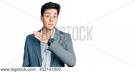 Young hispanic man wearing business clothes cutting throat with hand as knife, threaten aggression with furious violence