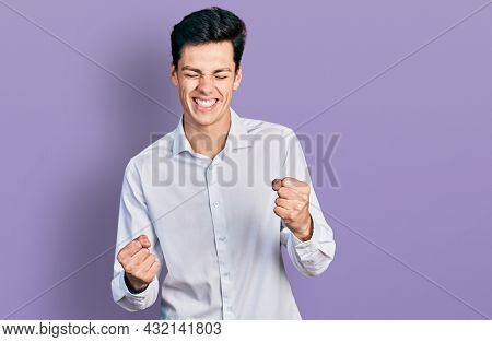 Young hispanic business man wearing business clothes very happy and excited doing winner gesture with arms raised, smiling and screaming for success. celebration concept.