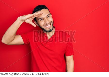 Hispanic man with beard wearing casual red t shirt very happy and smiling looking far away with hand over head. searching concept.