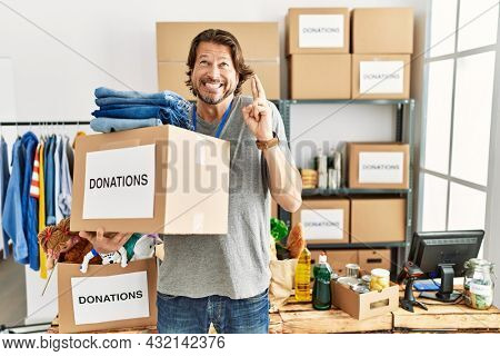 Handsome middle age man holding donations box for charity at volunteer stand gesturing finger crossed smiling with hope and eyes closed. luck and superstitious concept.