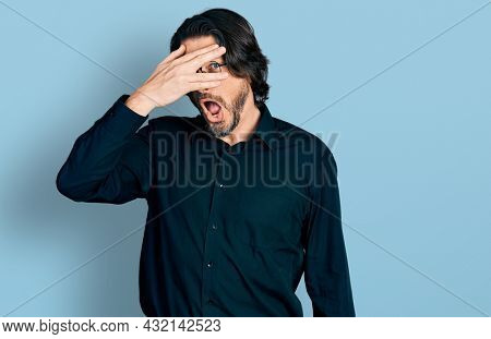 Middle age caucasian man wearing casual clothes and glasses peeking in shock covering face and eyes with hand, looking through fingers with embarrassed expression.
