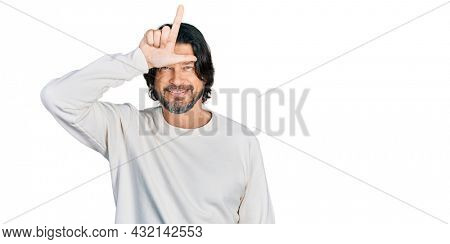 Middle age caucasian man wearing casual clothes making fun of people with fingers on forehead doing loser gesture mocking and insulting.
