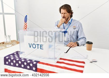 Handsome middle age man sitting at voting stand feeling unwell and coughing as symptom for cold or bronchitis. health care concept.