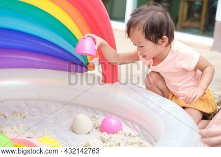 Cute Smiling Asian 2 Years Old Toddler Girl Child Playing With Kinetic Sand In Sandbox At Home, Nurs