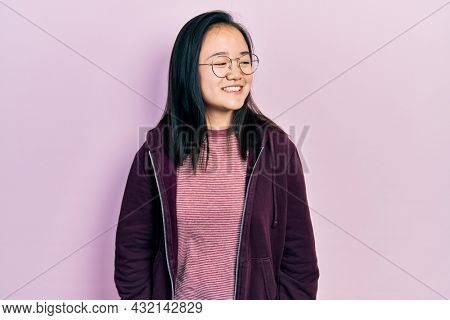 Young chinese girl wearing casual clothes and glasses looking away to side with smile on face, natural expression. laughing confident.