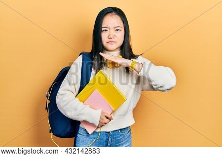 Young chinese girl holding student backpack and books cutting throat with hand as knife, threaten aggression with furious violence