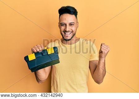 Young arab man holding toolbox screaming proud, celebrating victory and success very excited with raised arm