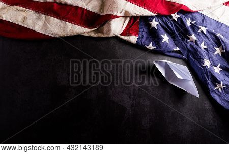 Happy Columbus Day Concept. Vintage American Flag With Paper Boat On Dark Stone Background.  Flat La