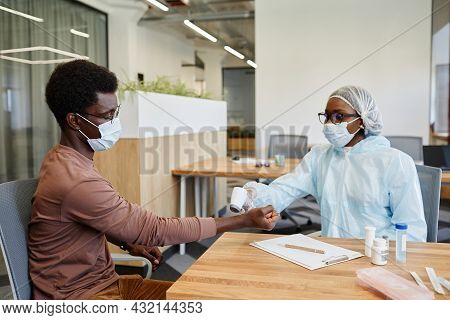 Medical Nurse In Ppe Using Infrared Non-contact Thermometer To Check Body Temperature Of Patient