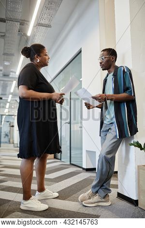 Serious African-american Entrepreneurs Comparing Data In Their Reports When Meeting In Corridor Of M