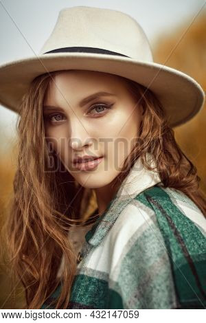 Portrait of a beautiful girl in a felt hat and a checkered flannel shirt on a background of autumn. Autumn beauty woman. Autumn colors.