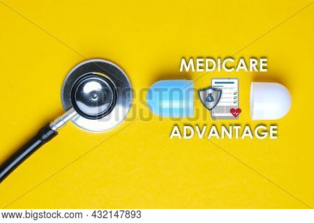 A Picture Of Stethoscope With Fake Capsule, Medicare Advantage Word, Tablet, Money Shield And Heart.