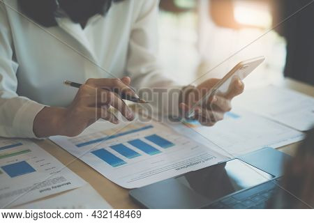 Business Woman Hand Holding Pen And Cell Phone With Bank Savings Account Application, Account Or Sav