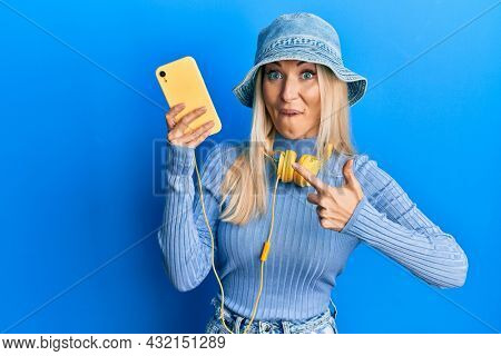 Young blonde woman using smartphone wearing headphones smiling happy pointing with hand and finger
