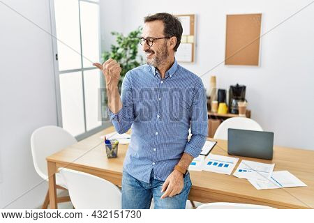 Middle age hispanic man with beard wearing business clothes at the office smiling with happy face looking and pointing to the side with thumb up.