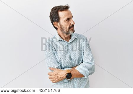 Middle age hispanic man with beard standing over isolated background looking to the side with arms crossed convinced and confident