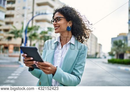 Young hispanic business woman wearing professional look smiling confident at the city using touchpad device