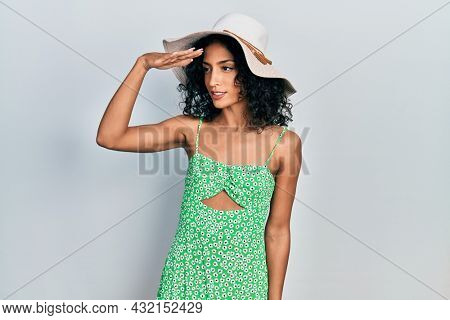 Young latin girl wearing summer hat very happy and smiling looking far away with hand over head. searching concept.
