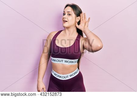 Young hispanic girl wearing sportswear smiling with hand over ear listening and hearing to rumor or gossip. deafness concept.