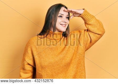 Young hispanic girl wearing casual clothes very happy and smiling looking far away with hand over head. searching concept.