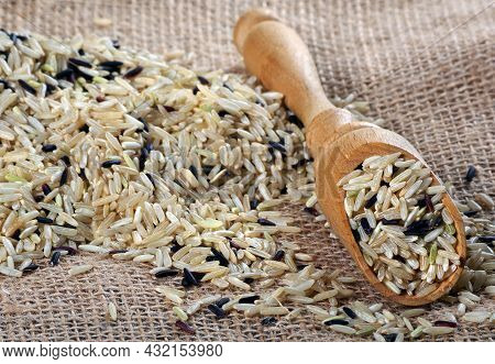 Brown Rice In A Wooden Scoop Close Up. Wild Brown Rice