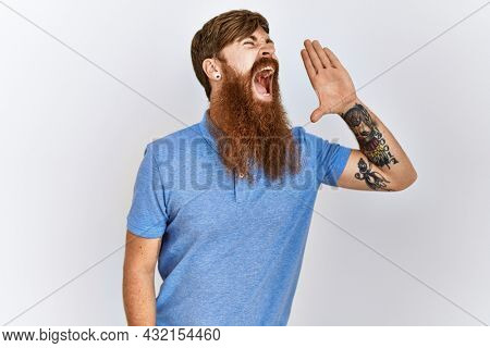 Caucasian man with long bear standing over isolated background shouting and screaming loud to side with hand on mouth. communication concept.