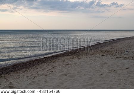 Sandy Coastline Covered With Wavy Tracks Goes Into Perspective Diagonally, Azure Sea With Smooth Sur