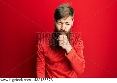 Redhead man with long beard wearing casual clothes feeling unwell and coughing as symptom for cold or bronchitis. health care concept.