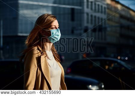 Beautiful Caucasian Woman Wearing Protective Medical Mask At City Street. Portrait Of Millenial Woma