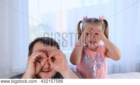 Funny Little Daughter 3 Years Old And Father Are Having Fun At Home, Making Funny Faces, Making Glas