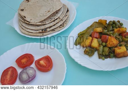 Indian Food - Matar Paneer Veg, Roti And Salad On White Plate With Light Blue Background