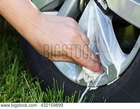 A Man Cleans The Rims Of A Car From Dirt And Bitumen From The Road Using Special Wipes And A Cleanin