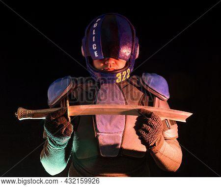 Cyberpunk Future Concept. Bionic Cyborg Police Officer With Short Samurai Sword Stands In Dark. Half