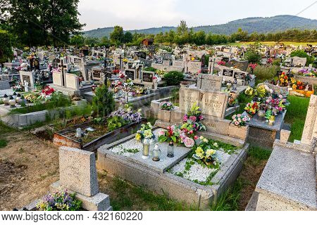 Milowka, Poland, 08.07.2021. Cemetery With Traditional Granite Graves Decorated With Colorful Artifi